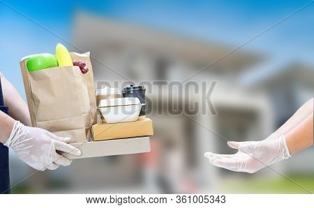 Deliveryman Holding Food Boxes And Coffee With Rubber Gloves. Online Shopping And Free Home Delivery