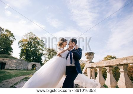 Bride And Groom At Wedding Day Walking Outdoors On Castle Territory. Bridal Couple, Newlywed Woman A