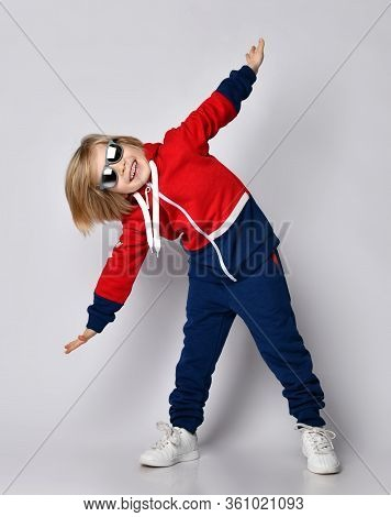 Happy Active Frolic Blond Kid Boy In Blue And Red Hoodie, Pants And Sunglasses Is Playing Aircraft P