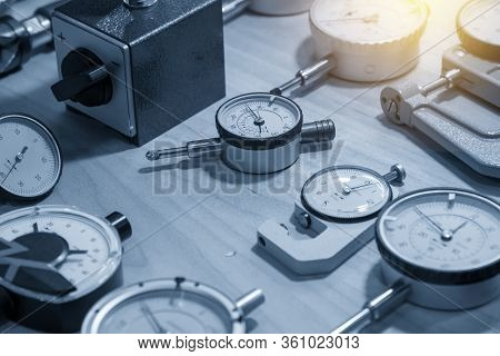 The Group Of Dial Indicator Gauge On The Table With Lighting Effect. The Group Of Measurement Instru
