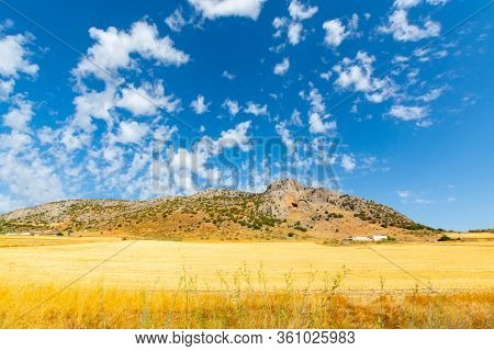 Andalusian Summer Landscape With Yellow Hills And Blue Sky With High White Clouds