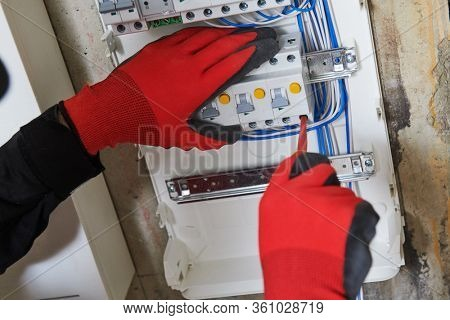 Electrician works with switchbox. installing circuit breaker