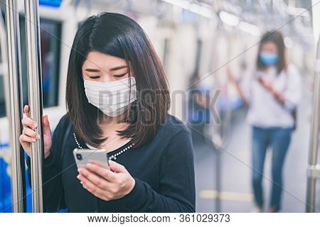 Young Asian Woman Wearing Protective Face Mask Using Smartphone In Underground Train Due To The Poll