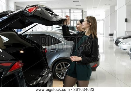 Friends Two Women Choose A Car At A Car Dealership And Check The Trunk.