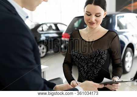 Car Rental And Insurance Concept, Young Salesman Receiving Money And Giving Cars Key To Customer Aft
