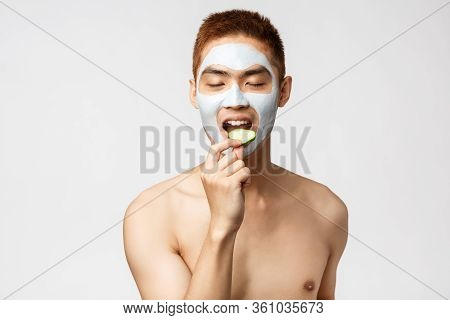 Beauty, Skincare And Spa Concept. Portrait Of Tender And Satisfied Asian Naked Man Close Eyes, Eatin
