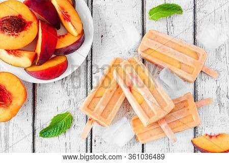 Summer Peach Yogurt Popsicles, Top View Table Scene Against A Rustic White Wood Background