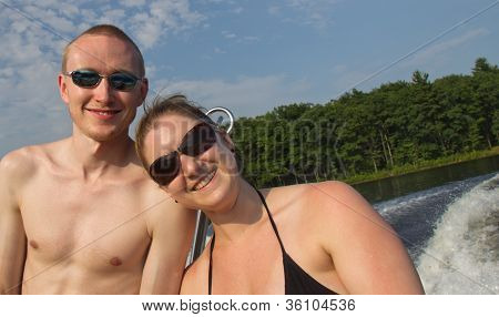 Young Couple In Swimsuits, Riding In Boat, Smiling And Looking At Camera