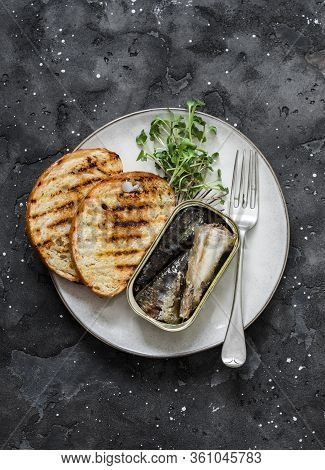 Grilled Bread, Canned Sardines, Micro Greens On A Dark Background, Top View. Delicious Breakfast, Ta