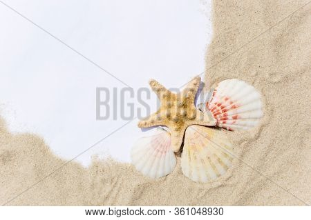 A Note Paper Framed With Sea Sand, Seashells And Starfish On Golden Sandy Beach On A Sunny Day. Summ