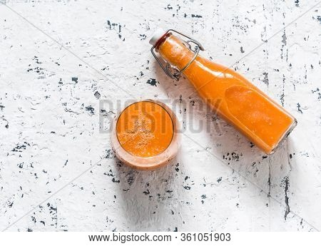 Glass And Takeaway Bottle With Mango Magic Smoothies On A Light Background, Top View.  Smoothies Wit