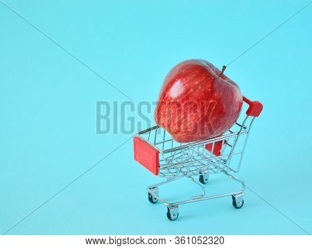 One Fresh Apple In Small Supermarket Pushcart Closeup.one Red Apple In A Small Shopping Cart With On
