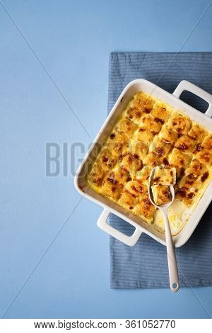 Homemade Gnocchi With Cheese Sauce In An Oven Tray On Blue Table. Flat Lay With Oven-fresh Cheese Gn