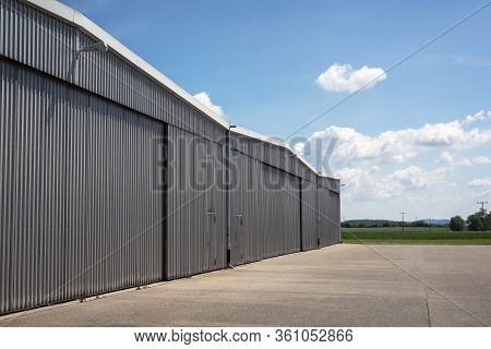 Metal Structure Hangar From A Private Airport In Germany. Hangar Exterior View On A Beautiful Summer