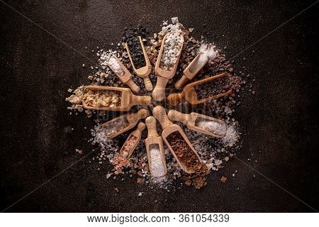 Still Life Of Different Types Of Salt In Wooden Scoop On Dark Background