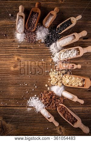 Different Types Of Salt In Scoop On Rustic Wooden Background