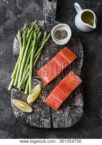 Raw Organic Salmon And Young Green Asparagus On A Rustic Chopping Board On A Dark Background, Top Vi