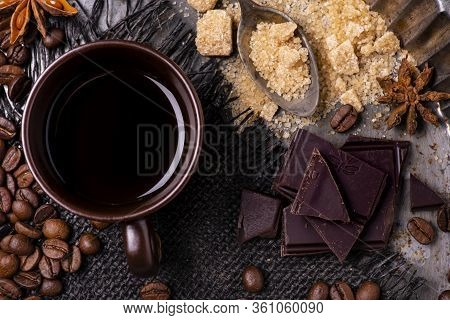Seen From Above. In The Foreground, A Cup Of Black Coffee, A Spoon With Brown Sugar, Some Pieces Of