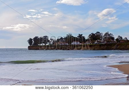 View Of Tree Lined Cliff Above Waves Rolling In On A Sandy Beach, In Santa Cruz, California, Usa