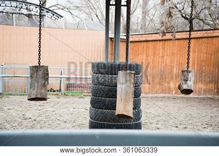 Toys For Entertaining Animals In The Zoo. Logs Hung On Chains For Hoofed Animals. Tires And Logs For