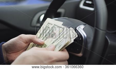 Man Counting Dollar Bills Sitting In A Car, Close Up Of Male Hands Count Money Cash. Concept Of Earn
