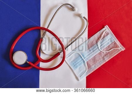 Phonendoscope And Facial Mask On French Flag. Outbreak Of Coronavirus Covid-19 In France. Hard Work