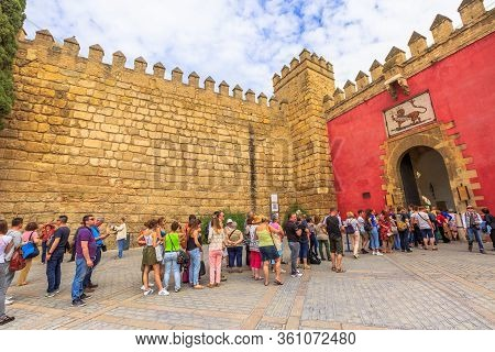 Seville, Andalusia, Spain - April 19, 2016: Row Of Tourists In Front Of Lions Gate, Entrance To Roya