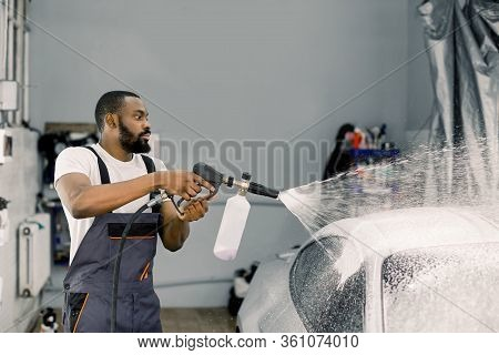 Close Up Portrait Of Young Pleasant African Car Wash Worker, Wearing Protective Overalls, Cleaning A