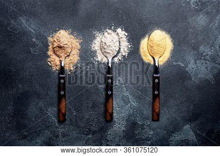 Various Vegetable Gluten Free Flour Corn,sesame,oat,coconut In Spoon On Dark Gray Background.alterna