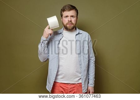 Alarmed Man Holds In Hands A Roll Of Toilet Paper, On A Green Background. Concept Of Paranoia Inflic