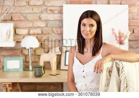 Portrait of attractive young woman smiling at home, looking at camera.