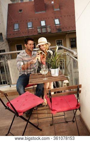 Young couple enjoying romantic evening on balcony, embracing, smiling.