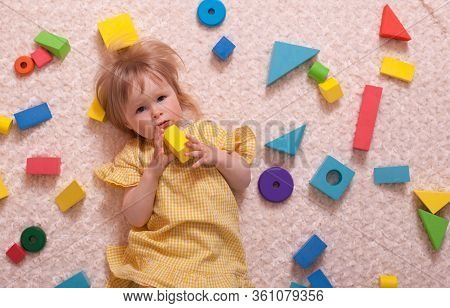 A Little Baby Girl In A Yellow Dress Playing At Home With A Constructor, Top View, Flat Layout. Conc