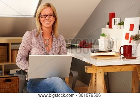 Happy woman working from home holding laptop computer on lap, sitting at home, smiling, looking at camera.