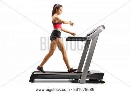 Full length profile shot of a fit young woman exercising on a treadmill and checking her arm-band isolated on white background