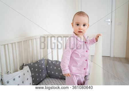 A Small Child In Pink Pajamas Stands In The Crib. The Kid Woke Up And Waits For His Parents To Get H