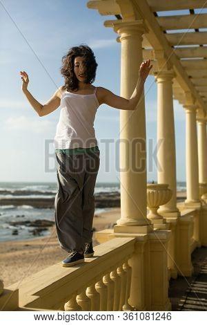 Asian woman walks along the railing of the ocean promenade.