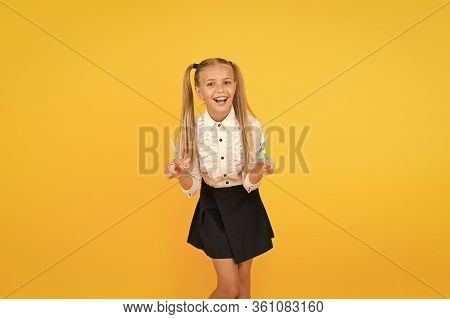 Learning With Fun. Happy Small Schoolchild Learning To Use Safe Scissors On Yellow Background. Littl