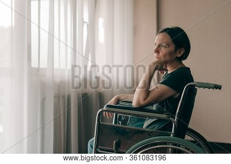 Depressed Sad Woman In Worn Wheelchair Looking Out The Window And Thinking, Lonely Disabled Adult Ca