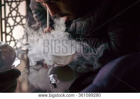 A Young Middle-eastern Man Smoking Hookah In The Bar. A Male Blowing Smoke. Man Smokes A Fragrant Or