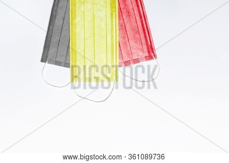 On Top Are 3 Medical Masks Of Black, Yellow And Red Colors On A Light Background. Masks Are Collecte