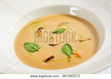 Chilean mussels soup in white bowl. Served main course close up. Seafood cream soup with roasted bread slice. Restaurant food portion, main course with toast. Dinner, gourmet meal in plate