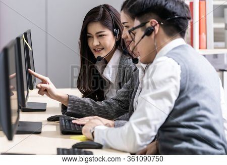 Young adult friendly and confidence operator asian man agent with headsets working in a call center with his colleague team working as customer service and technical support workplace in background.