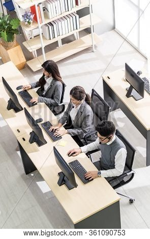 Top View Young adult friendly and confidence operator asian team agent with headsets working in a call center working as customer service and technical support workplace in background.
