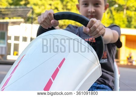 A Boy Riding Four Wheel Bike, Pedal Cart, Go-kart Rented In Entertainment Park In Summer, Children U