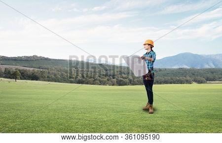 Young Woman In Safety Helmet Standing On Green Field With Paper Blueprint. Front View Of Architect I