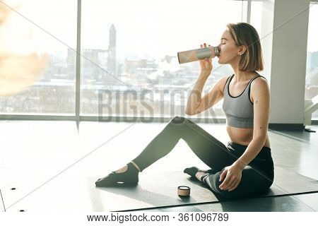 Young thirsty woman in activewear drinking water or tea after training while sitting on mat against large window in gym or leisure center