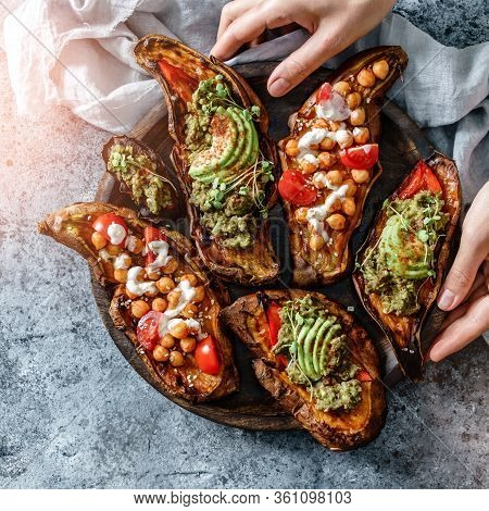 Hands Holding The Wooden Board With Baked Sweet Potato Toasts With Roasted Chickpeas, Tomatoes, Avoc