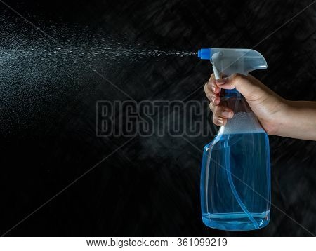 Close Up Of Female Hand Holding Foggy Spray Bottle And Spraying On Dark Background