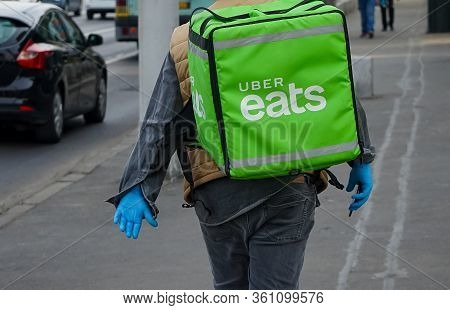 Bucharest, Romania - April 13, 2020: An Uber Eats Food Delivery Courier Delivers Food In Bucharest,